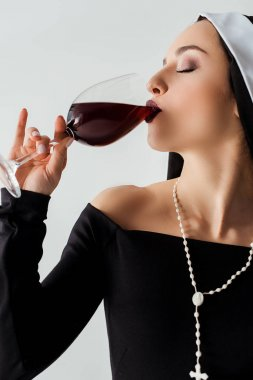 Attractive sensual nun drinking red wine from glass isolated on grey stock vector