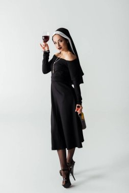 Attractive sexy nun holding glass and bottle of wine on grey stock vector