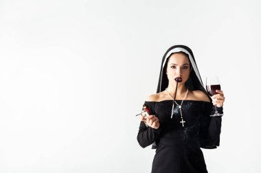 Attractive nun with lighter and glass of wine smoking a cigarette in mouthpiece isolated on grey stock vector