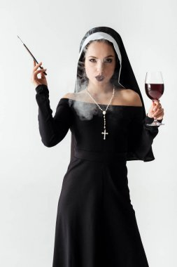Passionate nun with glass of wine smoking a cigarette in mouthpiece isolated on grey stock vector