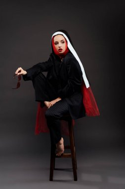 Barefoot stylish sexy nun posing in black suit and red scarf with sunglasses, on grey stock vector