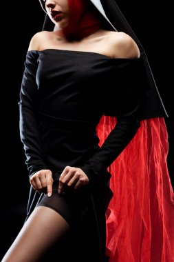 Cropped view of sexy nun in black dress, red scarf and stockings, isolated on black stock vector