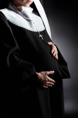 Cropped view of pregnant nun touching tummy on grey stock vector