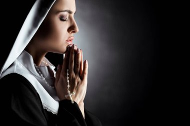 Beautiful young nun with closed eyes praying with cross on grey stock vector
