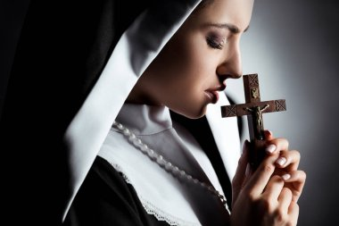 Sad young nun praying with cross on grey stock vector
