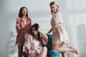Selective focus of multiethnic women with champagne glasses at bachelorette party in room