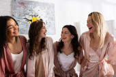 Mnohostranné ženy se smějí a dívají se na sebe v pokoji na rozlučce se svobodou