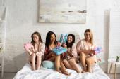 Multiculturális nők mosolyognak és ajándékdobozokat tartanak az ágyon a lánybúcsún.