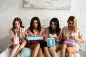Surprised multicultural friends opening gift boxes on bed at bachelorette party