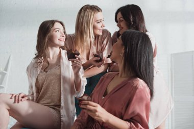 Low angle view of multicultural women with muffins looking at each other and smiling in room at bachelorette party stock vector