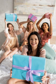 Selective focus of brunette girl showing present near multicultural friends holding gift boxes and smiling on bed