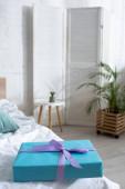 Selektivní zaměření modré dárkové krabice na posteli v pokoji