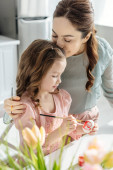 selective focus of mother kissing cute daughter painting easter egg near tulips