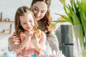 Selektiver Fokus von Tulpen nahe glücklicher Mutter und Tochter beim Bemalen von Ostereiern