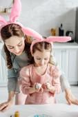 boldog anya és lánya nyuszifül nézi húsvéti tojás