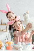 Photo happy mother looking at toy rabbit in hands of kid with bunny ears