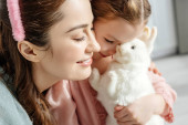selective focus of happy mother near cute kid with toy rabbit
