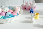 malované velikonoční vajíčka v blízkosti dekorativní zajíček a sklenice s barvou