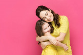 cheerful mother and daughter hugging isolated on pink
