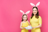 happy mother and daughter in bunny ears holding easter eggs isolated on pink