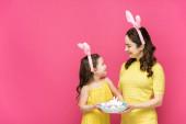 boldog anya és lánya nyuszifül tartja húsvéti tojás és nézik egymást elszigetelt rózsaszín