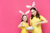 glückliche Mutter und Tochter in Hasenohren, die mit den Fingern auf Ostereier in rosa zeigen