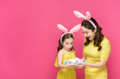 surprised mother and daughter in bunny ears looking at easter eggs isolated on pink