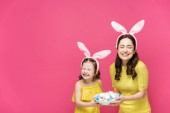 happy mother and daughter in bunny ears holding easter eggs and laughing isolated on pink