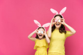 excited mother and daughter in bunny ears covering eyes with easter eggs isolated on pink