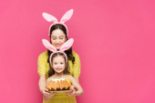 happy mother in bunny ears near daughter with easter cake isolated on pink