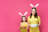 happy mother in bunny ears holding painted chicken eggs near daughter with easter cake isolated on pink