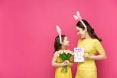 veselá matka v králičí uši drží blahopřání se šťastnými velikonočními písmeny v blízkosti dcery s tulipány izolované na růžové