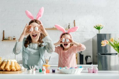 Excited mother and daughter in bunny ears covering eyes with painted chicken eggs near tulips and easter bread stock vector