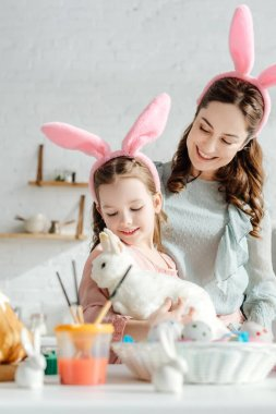 Happy mother looking at kid in bunny ears with toy rabbit stock vector