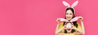 Panoramic shot of happy mother touching bunny ears of daughter covering eyes with easter eggs isolated on pink stock vector
