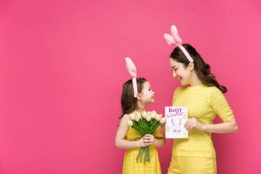 Cheerful mother in bunny ears holding greeting card with happy easter lettering near daughter with tulips isolated on pink stock vector