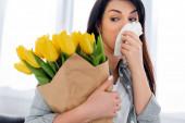 atraktivní žena s pylovou alergií při pohledu na tulipány