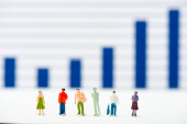 Selective focus of people figures on white surface with infographics at background, concept of equality