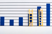 People figures with ladders near charts on white surface, equality concept