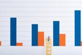 Lidé figurují na žebříku v blízkosti modrých a červených grafů na pozadí, rovnost koncept