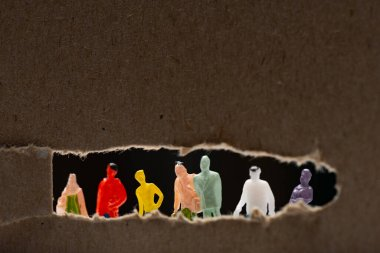 Selective focus of cardboard with hole and people figures isolated on black, concept of social equality