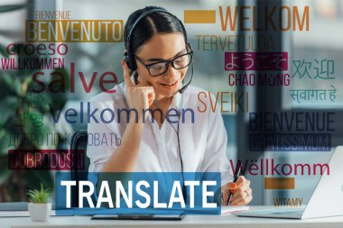 smiling asian translator working online with headset and laptop in office, welcome translation illustration