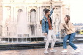 Excited woman and man looking at each other near fountain in city
