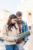 Thoughtful and concentrated couple with map in city
