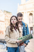 Worried and thoughtful girl holding map and looking away with boyfriend in city