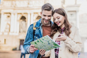 Selective focus of couple looking at map and smiling in city