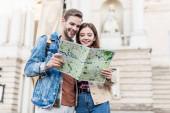 Pár se spolu dívá na mapu a usmívá se ve městě