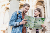 Low angle view of thoughtful boyfriend and happy girlfriend with map in city