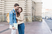 Selective focus of happy couple hugging and smiling with map in city