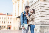 Selective focus of happy couple hugging and looking at each other with map in city
